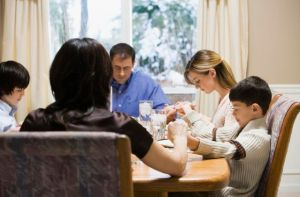 Parents and three children (9-17) praying and holding hands at table